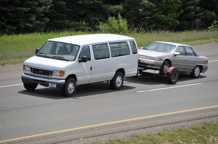Van with Tow Dolly Pulling Car
